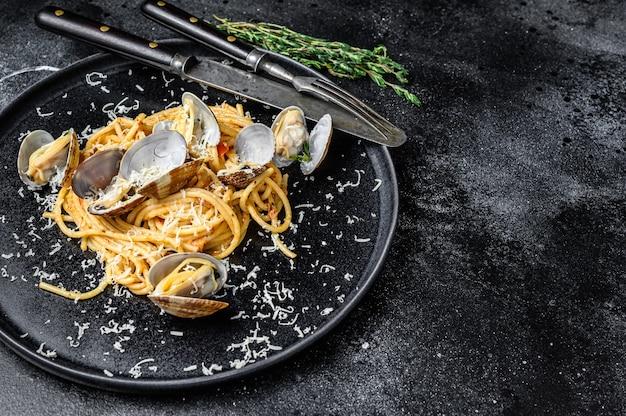 Makaron spaghetti z owocami morza z małżami vongole w talerzu. czarne tło. widok z góry. skopiuj miejsce.