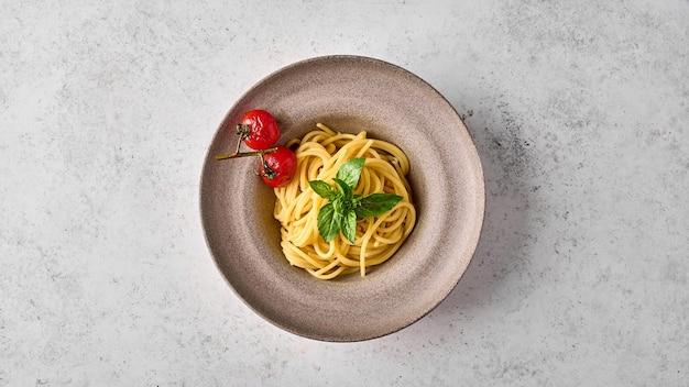 Makaron spaghetti z pieczonymi pomidorami cherry i bazylią na talerzu ceramicznym na jasnym tle płaski lay