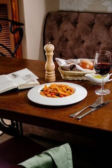 Makaron spaghetti z pomidorami i pietruszką na drewnianym stole