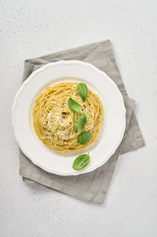 Makaron spaghetti z sosem pesto i świeżymi liśćmi bazylii w białej misce.