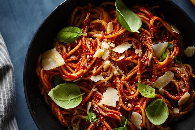 Makaron spaghetti z sosem pomidorowym i bazylią podawany w misce.