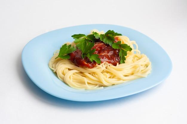 Makaron spaghetti z sosem pomidorowym i ziołami w niebieskim talerzu na białym tle