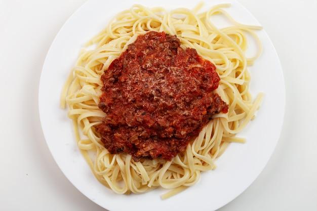 Makaron spaghetti z sosem ragu na białym talerzu