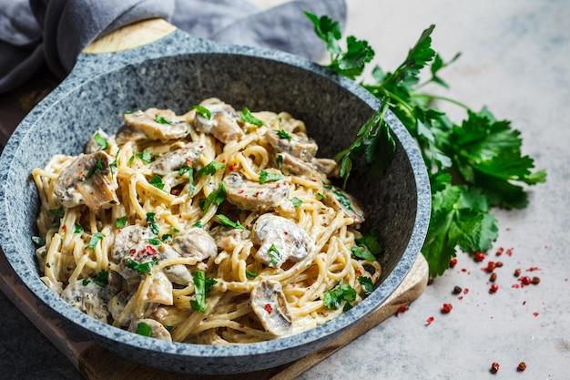 Makaron spaghetti z sosem śmietanowym, pieczarkami i natką pietruszki na szarej patelni, tło szare.