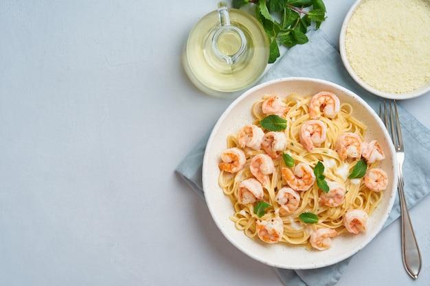Makaron spaghetti ze smażonymi krewetkami, sos beszamelowy, liść mięty na niebieskim stole, widok z góry, miejsce na kopię