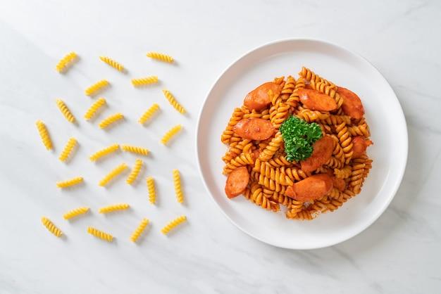 Makaron spirali lub spirali z sosem pomidorowym i kiełbasą. włoski styl jedzenia