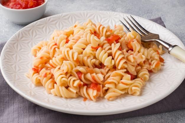 Makaron spiralny zmieszany z pomidorami cherry i sosem pomidorowym na talerzu.