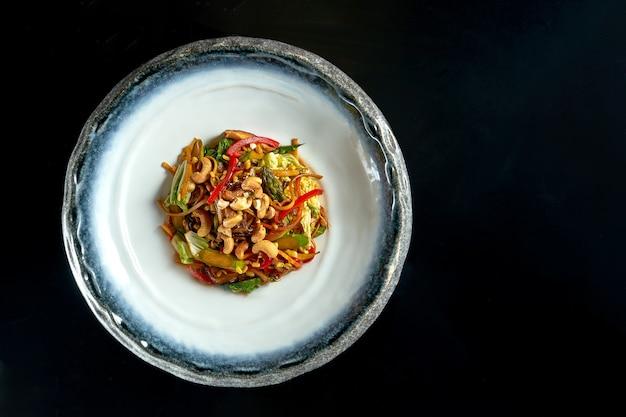 Makaron szklany słodko-kwaśny z wieprzowiną, warzywami i cebulą, podawany w białej misce.