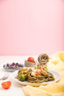 Makaron szpinakowy zielony tagliatelle z pomidorami, groszkiem i mikrogranulkami na białym i różowym tle.