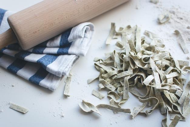 Makaron tagliatelle objęte mąki z drewnianym wałkiem na białym tle