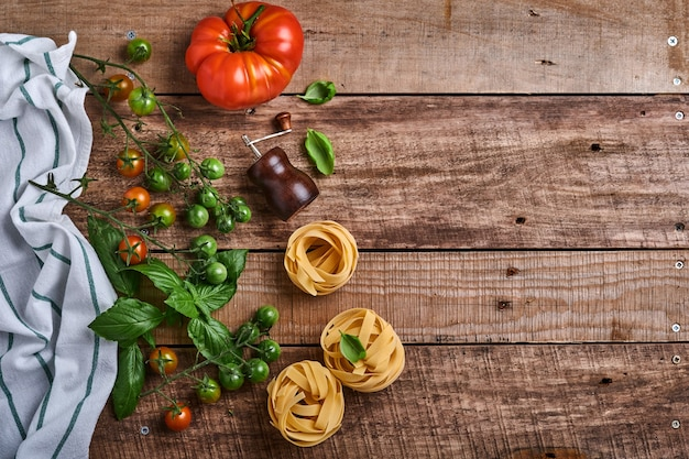 Makaron tagliatelle, przyprawy, bazylia i świeże pomidory na starym drewnianym stole w stylu rustykalnym. gotowanie żywności i tło makaronu. widok z góry z miejsca na kopię.