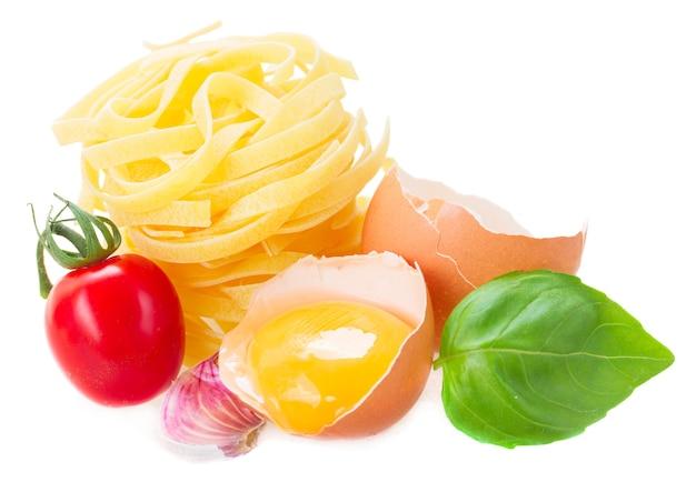 Makaron tagliatelle surowego z żółtkiem i pomidorem na białym tle