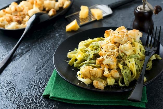 Makaron tagliatelle w kremowym sosie z pieczonym kalafiorem na talerzu na ciemnej powierzchni