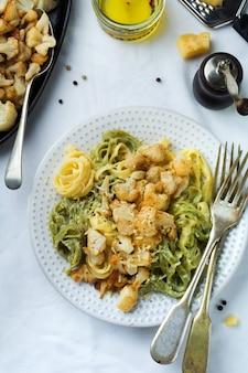 Makaron tagliatelle w kremowym sosie z pieczonym kalafiorem na talerzu na jasnej powierzchni
