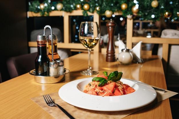 Makaron tagliatelle z pomidorami na białym talerzu na stole w restauraci.