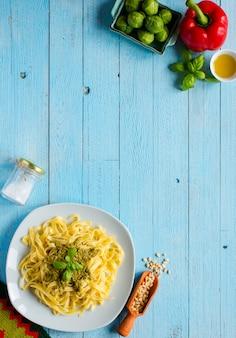 Makaron tagliatelle z sosem pesto i innymi warzywami na drewnianym tle. widok z góry