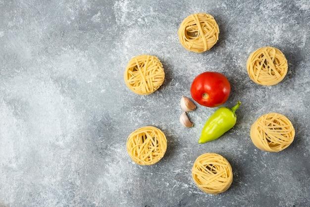 Makaron tagliatelle z surowym gniazdem i warzywami na tle marmuru.