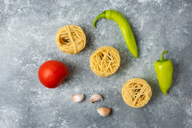Makaron tagliatelle z surowymi gniazdami i warzywami na marmurowym stole.