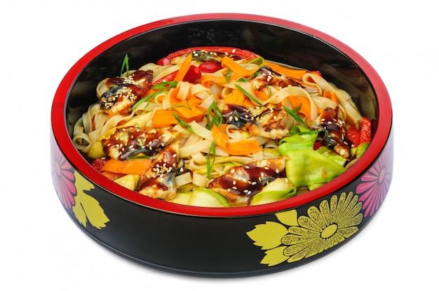Makaron tagliatelle z wędzonym węgorzem i warzywami w czarnym pucharze odizolowywającym na bielu