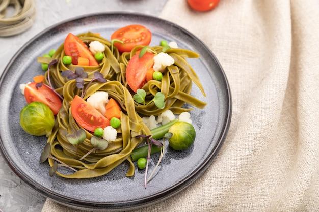 Makaron tagliatelle z zielonym szpinakiem z pomidorami, groszkiem i mikrogielonymi kiełkami na szarym betonowym tle i lnianą tkaniną.
