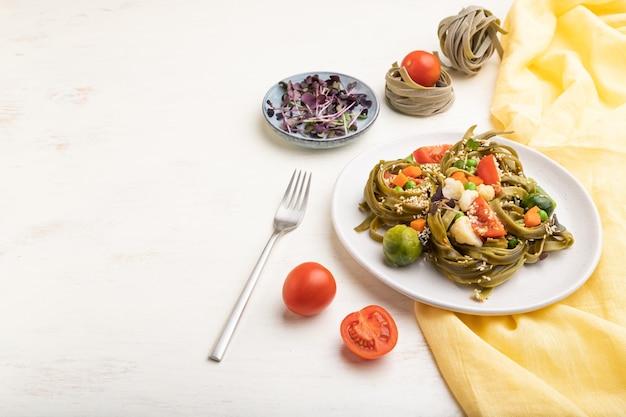 Makaron tagliatelle ze szpinakiem zielonym z pomidorem, groszkiem i mikrogielonymi kiełkami na białym drewnianym stole i żółtym materiale. widok z boku, miejsce na kopię.
