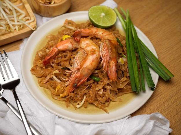 Makaron tajski opalany mieszanką z krewetkami podawany na drewnianym stole z limonką, kiełkami fasoli i szczypiorkiem, tradycyjne tajskie jedzenie