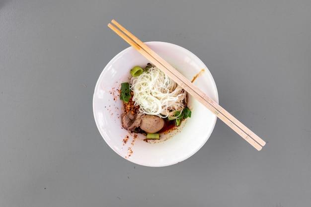 Makaron tajski suchy wermiszel z wieprzowiną w małej białej miseczce na szarym rustykalnym stole.