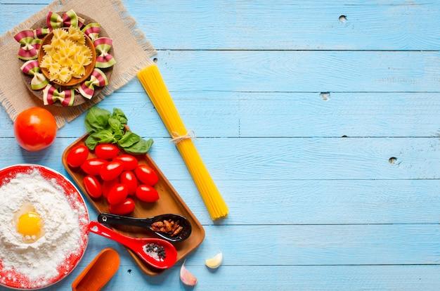 Makaron tło kilka rodzajów suchego makaronu z warzywami i ziołami. widok z góry