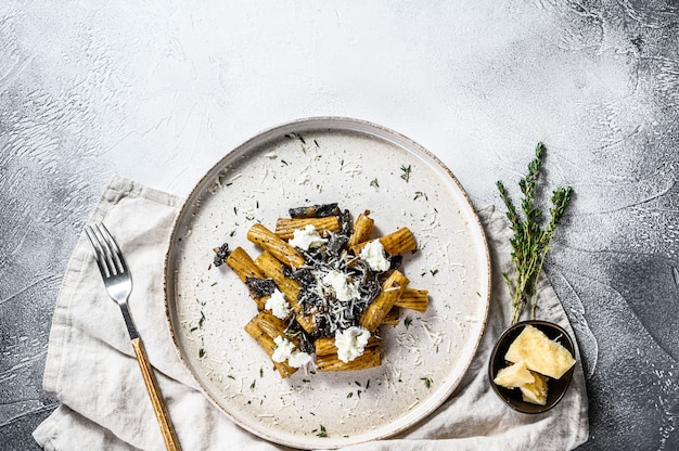 Makaron tortiglioni z czarną truflą, białym grzybem, sosem śmietanowym i serem ricotta. szare tło, widok z góry. miejsce na tekst