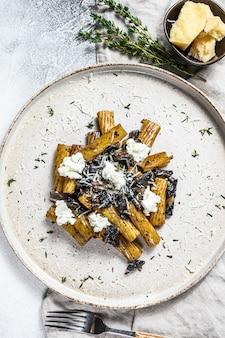 Makaron tortiglioni z czarną truflą, białym grzybem, sosem śmietanowym i serem ricotta. szare tło. widok z góry