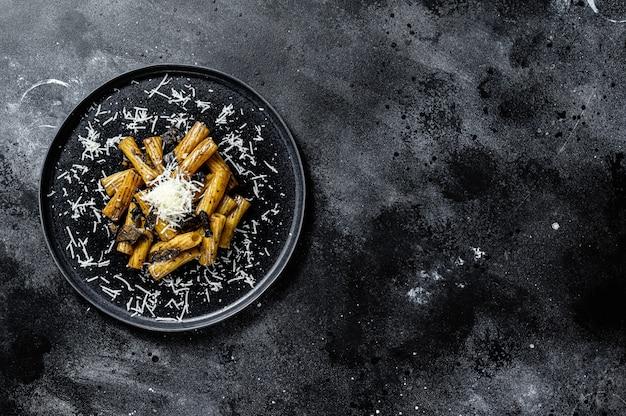 Makaron tortiglioni z czarną truflą i borowikami szlachetnymi, biały grzyb. czarne tło. widok z góry. miejsce na tekst