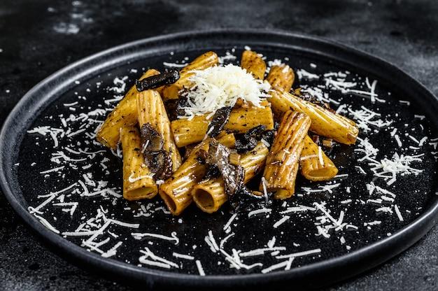 Makaron tortiglioni z czarną truflą i borowikami szlachetnymi, biały grzyb. czarne tło. widok z góry