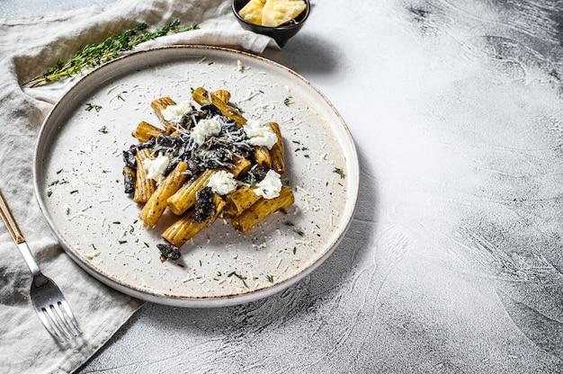 Makaron tortiglioni z czarną truflą i borowikami szlachetnymi, biały grzyb. szare tło. widok z góry. miejsce na tekst