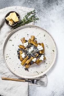 Makaron tortiglioni z czarną truflą i borowikami szlachetnymi, biały grzyb. szare tło. widok z góry