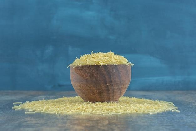 Makaron vermicelli rozsypany z pełnej miski, na marmurowej powierzchni.