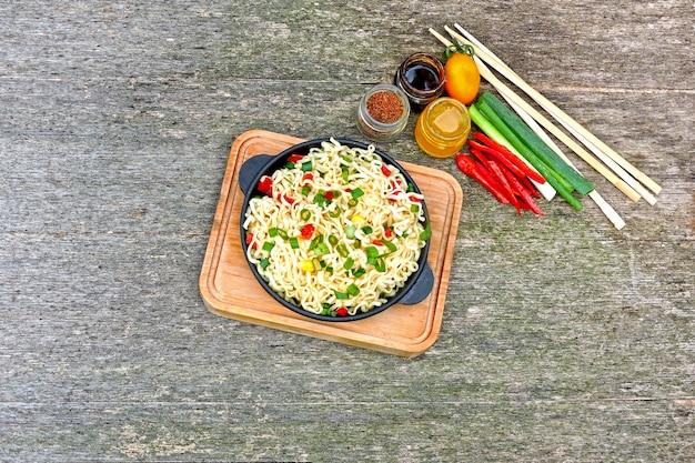 Makaron w chińskim stylu na żeliwnej patelni na drewnianym stojaku. chiński makaron z warzywami i papryką chili. pikantny wegetariański makaron z warzywami.