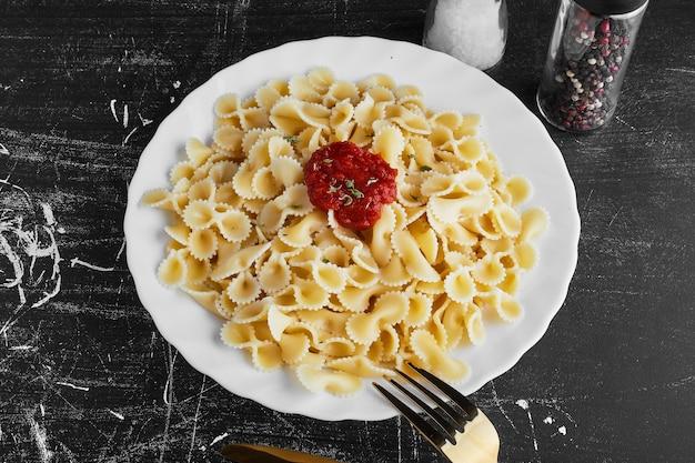 Makaron w czerwonym sosie chili na białym talerzu.