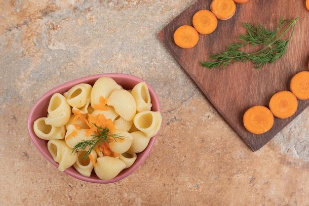 Makaron w kształcie muszli z plastrami marchewki i koperkiem w misce.