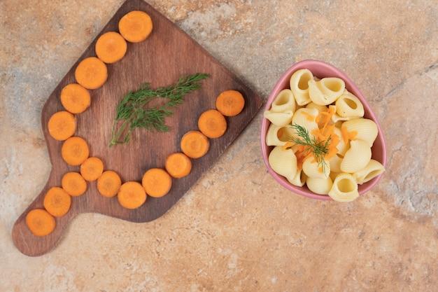 Makaron w kształcie muszli z plastrami marchwi i koperkiem w misce