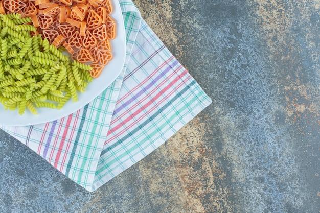 Makaron w kształcie paleniska z makaronem fusilli na talerzu, na ręczniku, na marmurowej powierzchni.