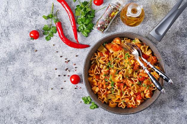Makaron w kształcie serca z kurczakiem i pomidorami w sosie pomidorowym. widok z góry