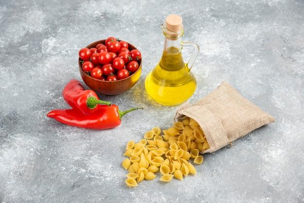 Makaron w rustykalnych torebkach podawany z pomidorkami koktajlowymi, chilli i oliwą z oliwek.