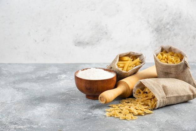 Makaron w rustykalnym koszu z wałkiem do ciasta i drewnianym kubkiem mąki dookoła.