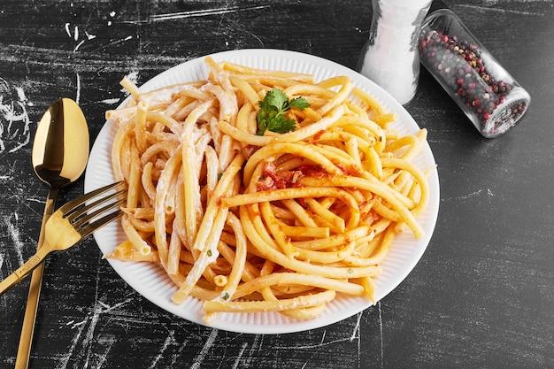Makaron w sosie pomidorowym na białym talerzu.