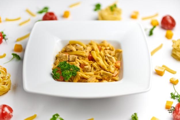 Makaron w sosie pomidorowym z kurczakiem, pomidorami ozdobionymi natką pietruszki na drewnianym talerzu