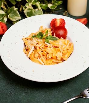 Makaron w sosie pomidorowym z siekanym parmezanem, pomidorem i bazylią.
