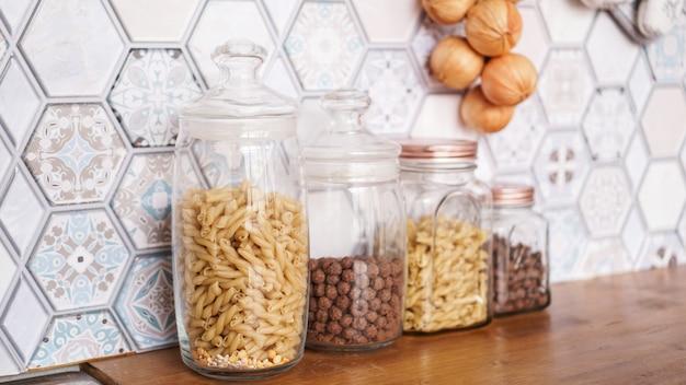 Makaron w szklanych słoikach. makaron na drewnianym blacie w nowoczesnej jasnej kuchni.