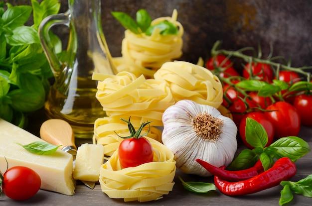 Makaron, warzywa, zioła i przyprawy do włoskiego jedzenia na drewnianym stole.