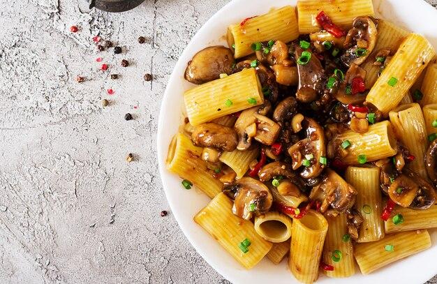 Makaron wegetariański rigatoni z pieczarkami i papryczkami chili w białej misce na szarym stole. wegańskie jedzenie. leżał płasko. widok z góry
