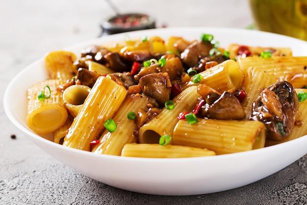 Makaron wegetariański rigatoni z pieczarkami i papryczkami chili w białej misce na szarym stole. wegańskie jedzenie.